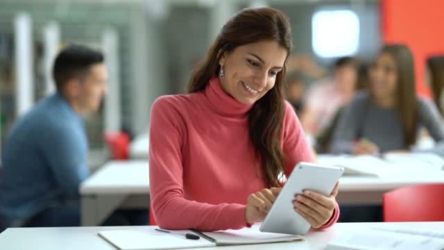 休憩を取って、デジタル タブレットに彼女のソーシャル メディアをチェック ライブラリのかなり女子学生 - 公共図書館点の映像素材/bロール