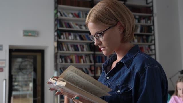 Hübsche Studentinnen, die ein Buch in der Bibliothek lesen, die fokussiert ist