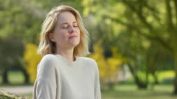 Pretty female taking a deep breath in front of colorful park scenery