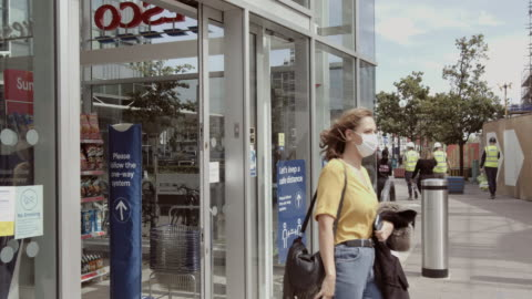 pretty female wearing protective face mask walking out of supermarket - shopping stock videos & royalty-free footage