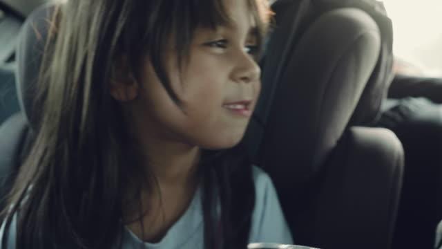 子供のカーシートでかわいい女の子 - 車内点の映像素材/bロール