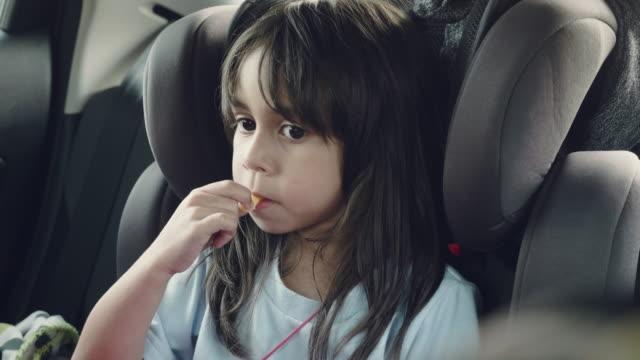 vídeos de stock, filmes e b-roll de menina bonita em um assento de carro infantil - bebês meninas