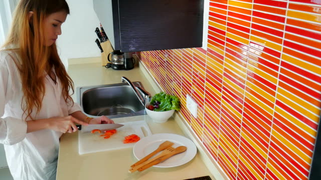 pretty girl in her kitchen cutting vegetable ingredients. - cutting board stock videos and b-roll footage