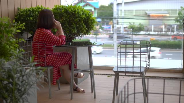 vidéos et rushes de jolie fille dans les pourparlers de robe rouge sur le téléphone dans le jardin - robe rouge