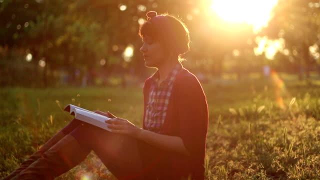 Hübsche Mädchen liest ein Buch im park