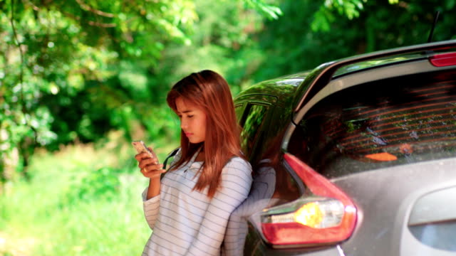 pretty girl talking by phone after car incident - tow truck driver stock videos and b-roll footage