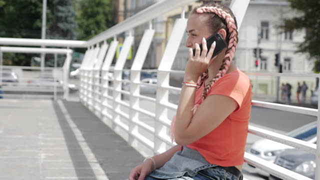 pretty girl talking on phone while sitting outdoors - dungarees stock videos and b-roll footage