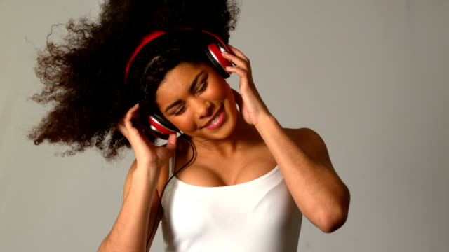 Pretty girl with afro jumping and listening to music