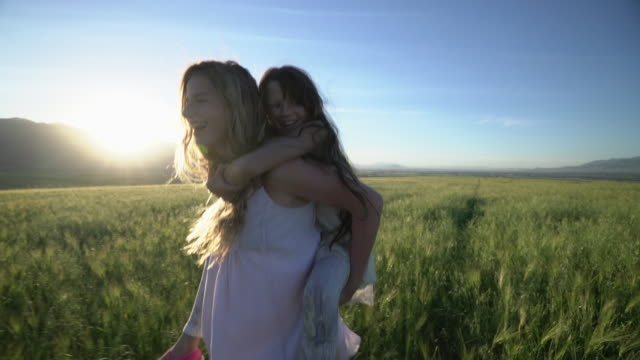 ms ts sm pretty girls playing in a field. - piggyback stock videos & royalty-free footage