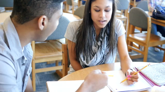 Pretty Hispanic teen girl in high school library studying with African American male student