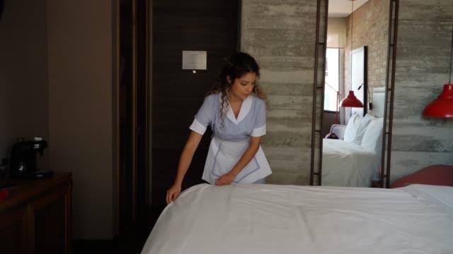 vídeos y material grabado en eventos de stock de cuidador de casa linda trabaja en un hotel haciendo una cama - hospitalidad