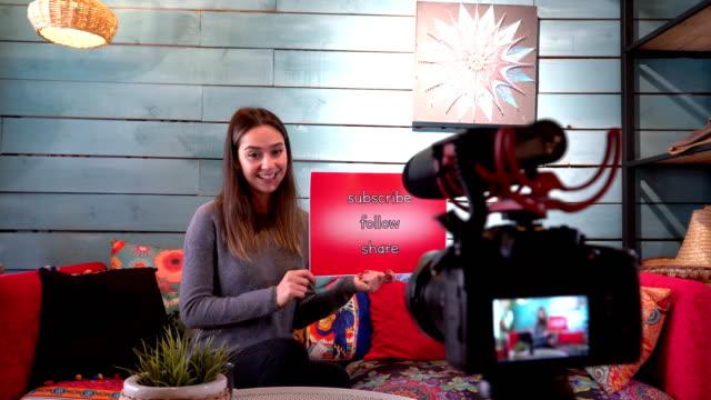 vídeos y material grabado en eventos de stock de pretty influencer está mostrando ''subscribe - follow - share '' palabras con cartón - entrevista grabación