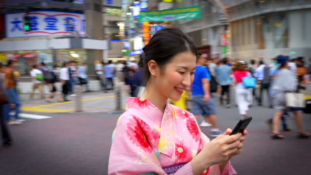 Schöne japanische Frau In einen Kimono eine SMS