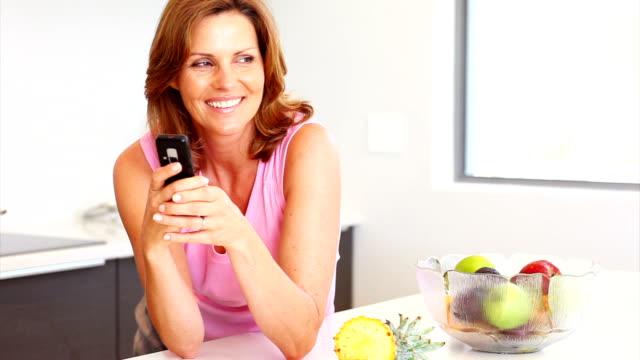bella donna usando il suo cellulare in cucina - quarantenne video stock e b–roll