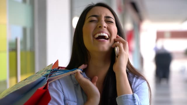 vídeos de stock e filmes b-roll de pretty latin american woman on a phonemail laughing and looking very happy at the mall - centro comercial