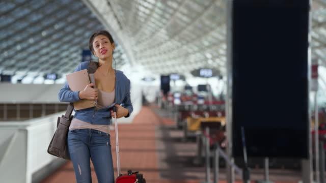 vídeos y material grabado en eventos de stock de pretty latina female waits at airport with her suitcase - carrying