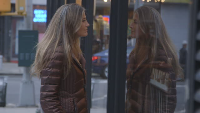 stockvideo's en b-roll-footage met a pretty, mature woman looking into a brooklyn shop window - etalage