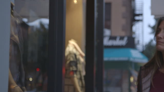 A pretty, mature woman looking into a Brooklyn shop window