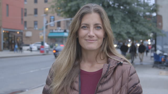 A pretty, mature woman smiling into the camera on a Brooklyn street