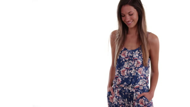 Pretty millennial woman in romper looking at camera on solid white background