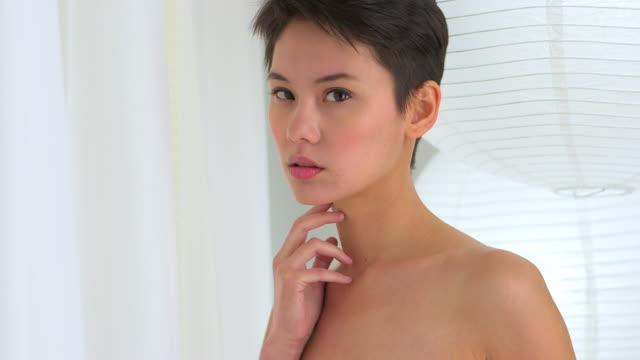 stockvideo's en b-roll-footage met pretty mixed race asian woman standing in living room - natuurlijk haar