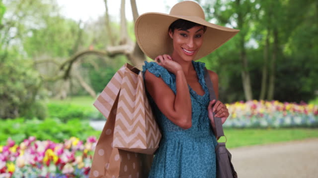 vídeos de stock, filmes e b-roll de pretty mixed race millennial woman posing in garden with shopping bags - shopaholic