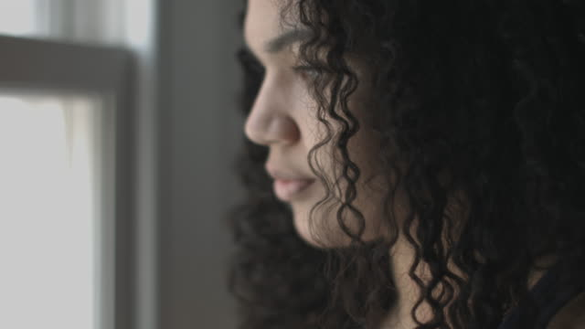 pretty mixed race woman looking out of window - looking through window stock videos & royalty-free footage