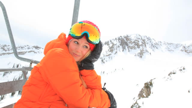 a pretty skier rides a chairlift and enjoys the view. - seggiovia video stock e b–roll