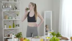 Pretty slender woman drinking green herbal cocktail and smiling at camera. Confident young Caucasian girl using detox drink for weight control and health care. Beauty, advertising, lifestyle.