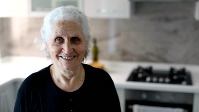 vídeos de stock e filmes b-roll de dolly : pretty smiling senior woman in the kitchen at home - jovem de espírito