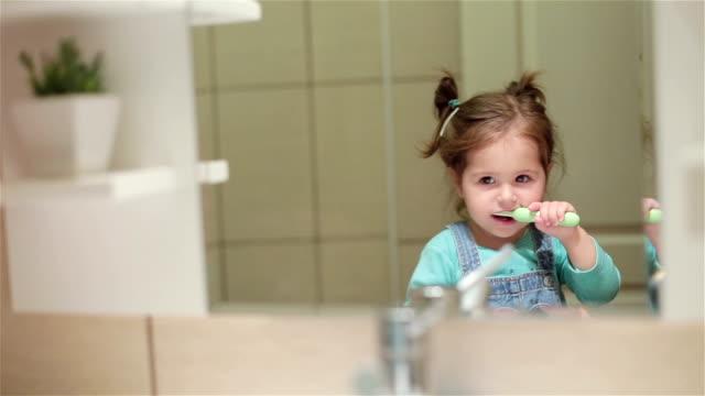 stockvideo's en b-roll-footage met mooie peuter meisje haar tanden poetsen - menselijk gebit