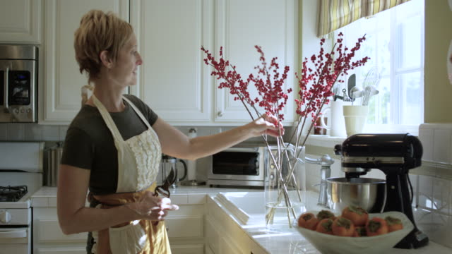 pretty woman arranging flowers in the kitchen - decoration stock videos & royalty-free footage