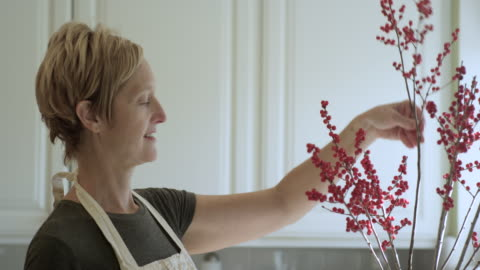 pretty woman arrangera blommor i köket - 50 54 år bildbanksvideor och videomaterial från bakom kulisserna