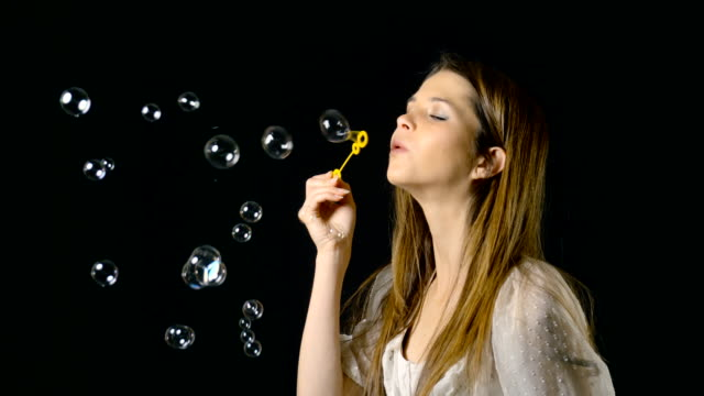 pretty woman blowing bubbles slow motion - bubble wand stock videos & royalty-free footage