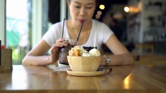 チョコレート フラッペを食べたり、カフェでスマート フォンを使用してのきれいな女性 - サンデー点の映像素材/bロール