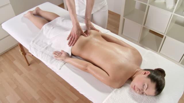 vídeos de stock, filmes e b-roll de hd: linda mulher, desfrutando de uma massagem relaxante nas costas - cuidado com o corpo