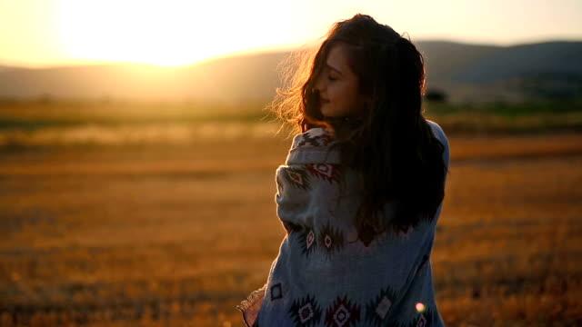 stockvideo's en b-roll-footage met mooie vrouw genieten van zonsondergang - gekruld haar