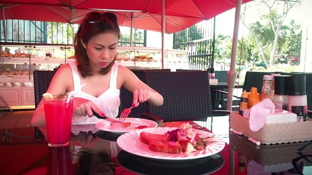 Pretty woman enjoying the taste of grilled steak in restaurant