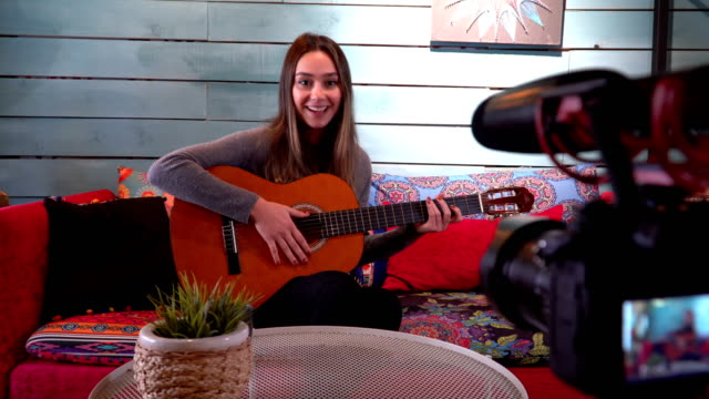 pretty woman giving guitar lesson on internet with video tutorial - musician stock videos & royalty-free footage