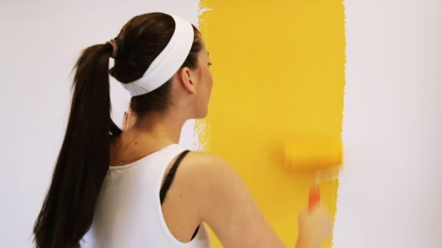 vídeos de stock, filmes e b-roll de linda mulher pintura - parede