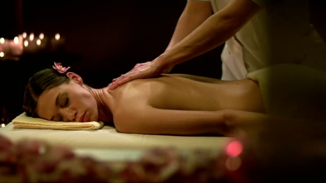 pretty woman relaxing in spa salon - massage table stock videos & royalty-free footage