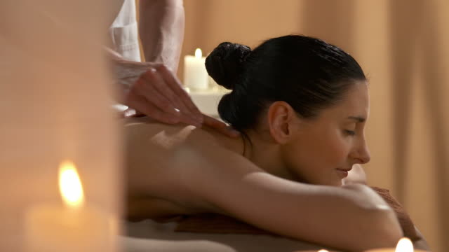 hd: pretty woman relaxing while getting shoulder massage - massage table stock videos & royalty-free footage