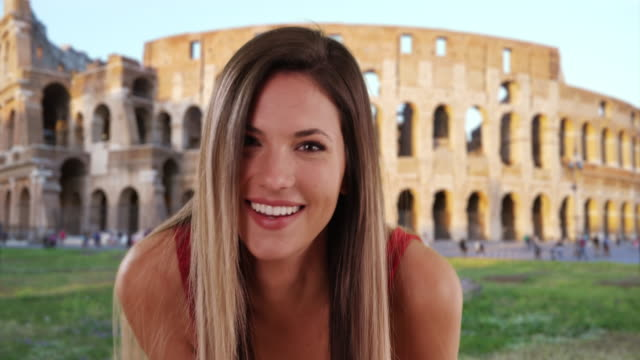 Pretty woman smiling and blowing kisses to camera outside by Colosseum in Rome