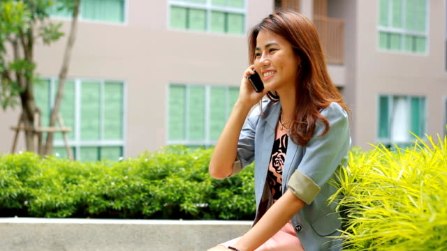 pretty woman talking on mobile phone with smile face - indonesian ethnicity stock videos & royalty-free footage
