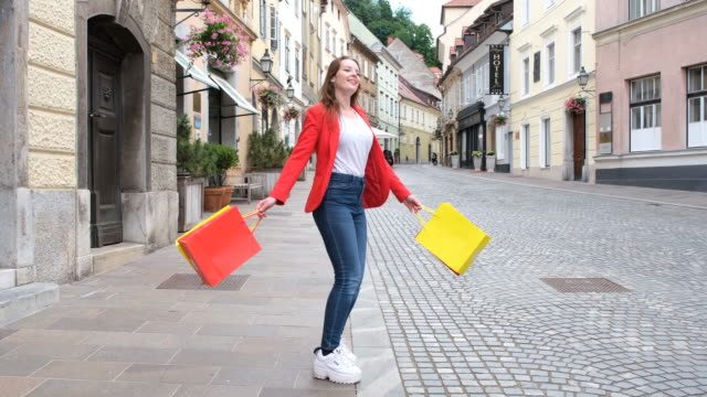 pretty woman walking down the street with shopping bags - shopaholic stock videos & royalty-free footage