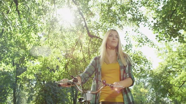 vídeos de stock, filmes e b-roll de linda mulher caminhando pelo parque, enquanto empurrando sua bicicleta - mulheres jovens
