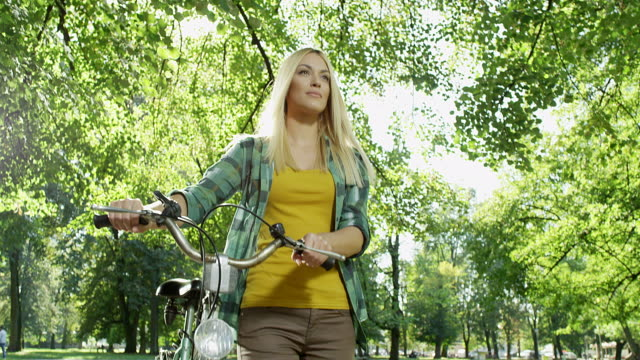 pretty woman walking through park while pushing her bicycle - capelli biondi video stock e b–roll