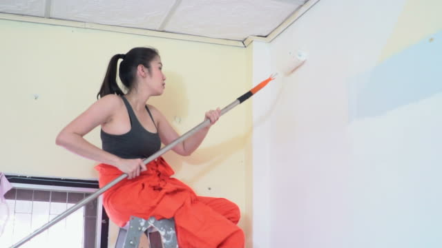 pretty woman wall with paint roller - artista video stock e b–roll