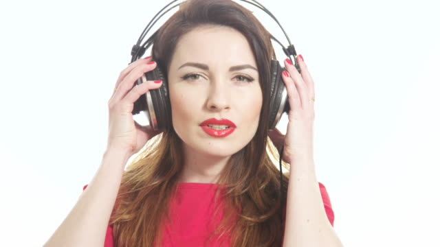 pretty woman wearing red lipstick listening to the music touching big headphones takes off ear cup saying what isolated on white background close up shot - red lipstick stock videos & royalty-free footage