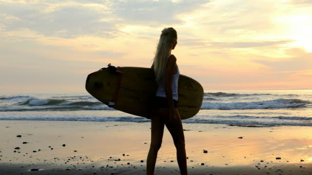 vídeos de stock, filmes e b-roll de mulher bonita com prancha caminhando na praia ao pôr do sol - olhando para vista